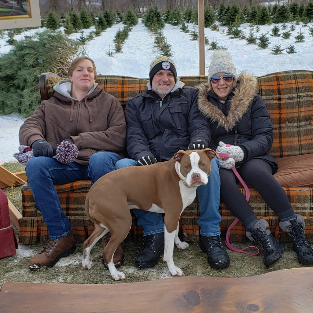 A family with their pit bull sitting on a couch