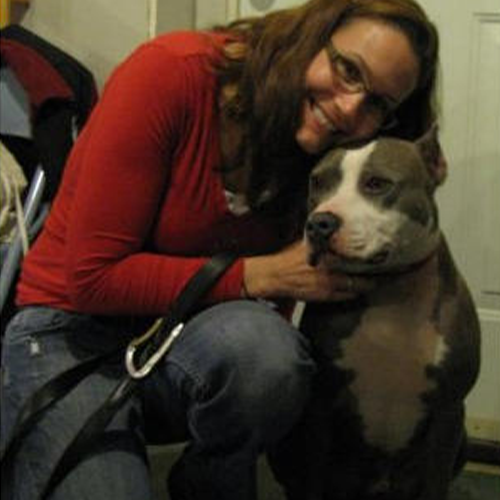 Bruno, Therapy dog being hugged by a women in a red top and jeans